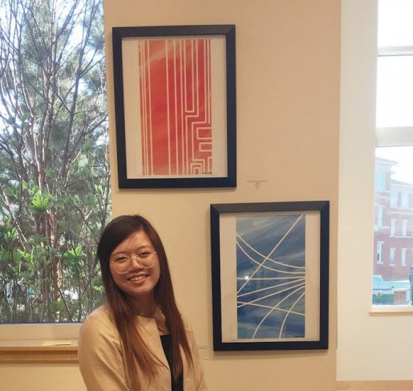 Dani Ng in front of her artwork displayed in Student Union Art Gallery